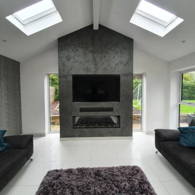 Concrete effect flor to ceiling media wall and integrated fireplace
